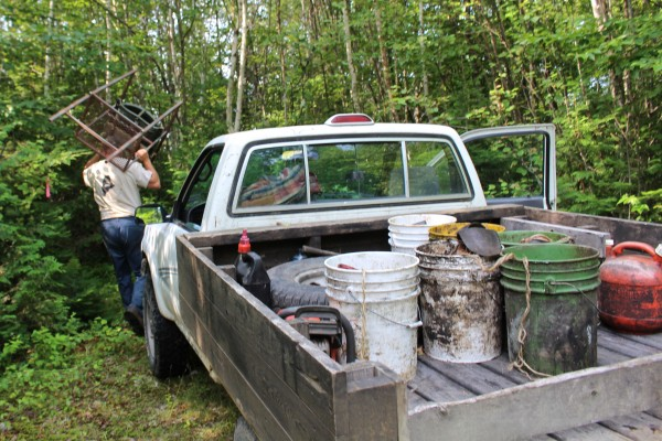 Buckets of bear bait - pastries and skinned beaver - sit in the pickup of Troy White, registered master Maine guide and owner of Mid Maine Outfitters, on July 29, on an old woods road near Lincoln. White, carrying a custom-made tree stand, is delivering the bait to various bait sites throughout the woods in preparation of Maine's fall bear hunt.