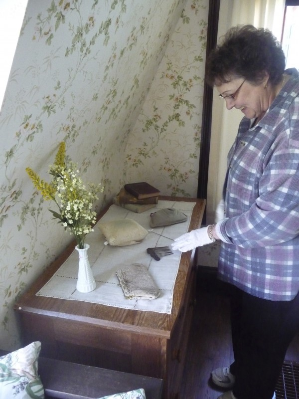 Darlene Savage of Campobello Island, New Brunswick, dusts Eleanor Roosevelt's belongings, such as purses and a hair comb, on a bureau in the Roosevelt Cottage at the Roosevelt Campobello International Park.