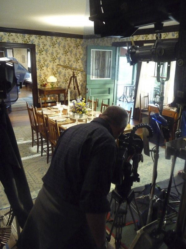 Filmmaker Paul Barnes sets up a shot in the dining room of the Roosevelt Cottage at the Roosevelt Campobello International Park.