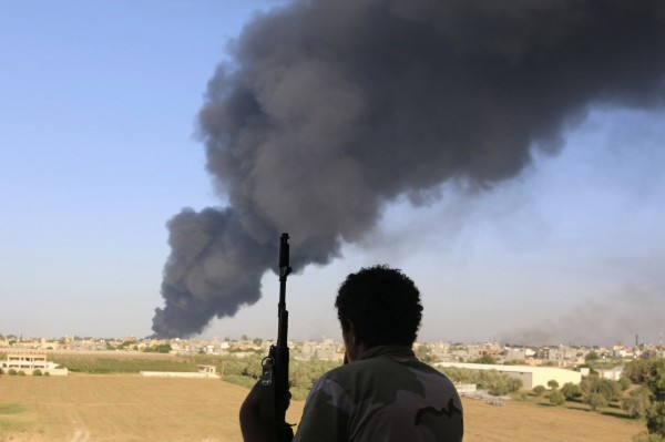 A fighter from Zintan brigade watches as smoke rises after rockets fired by one of Libya's militias struck and ignited a fuel tank in Tripoli August 2, 2014. On Saturday, sporadic shelling resumed in the capital after two days of relative calm. Plumes of black smoke rose over the south of Tripoli from a burning fuel tank at the airport's fuel depot.