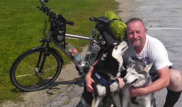 Randolph Westphal, with his dogs Nanook and her son, Chinook, outside Fireside Inn in Bangor on Sunday, Aug. 3 is spreading cancer awareness and biking around the world, encouraging people to never give up. He will be riding around Bangor Monday and plans to head north to Canada in preparation for a flight home to Germany to have surgery in September.