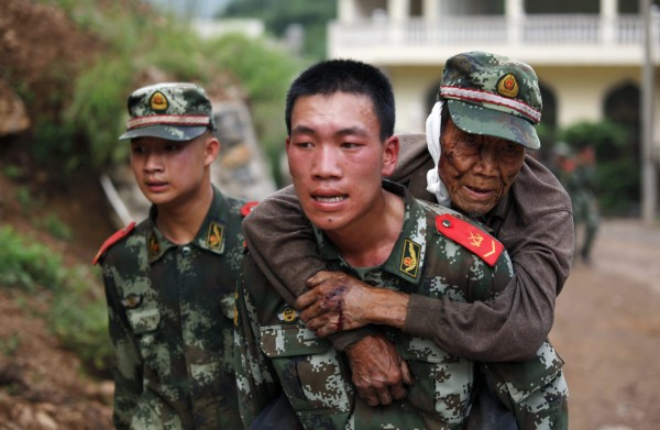 A paramilitary policeman carries an elderly man on his back after an earthquake hit a remote area of Yunnan province on Saturday.