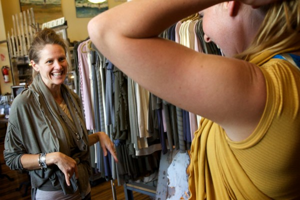 Clothing designer Roxi Suger takes a look at model Paige Mooney as she tries on a piece from Suger's Angelrox collection in Biddeford on Tuesday. Sugar's creations will grace the catwalk at the Biddeford Ball this weekend.