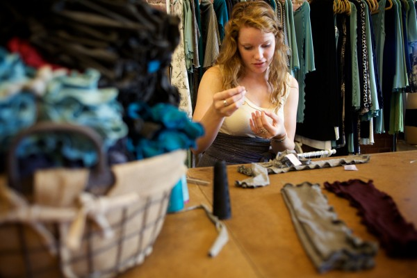 Mariah Foss hand sews final touches on clothing from Roxi Suger's Angelrox collection in Biddeford on Tuesday. About 40 models will show off Suger's designs at the Biddeford Ball on Saturday night.