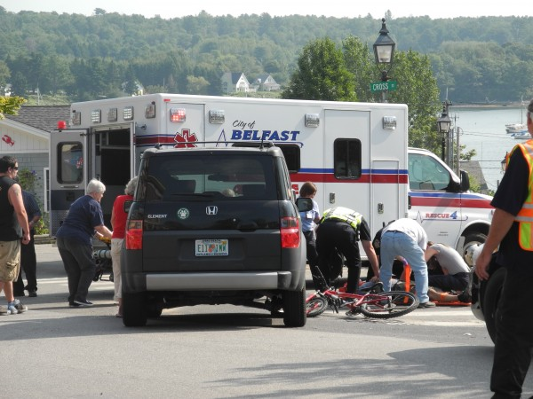 Emergency crews tend to a cyclist who police said was hurt Wednesday morning when a vehicle ran into him at the corner of Main and Cross streets.
