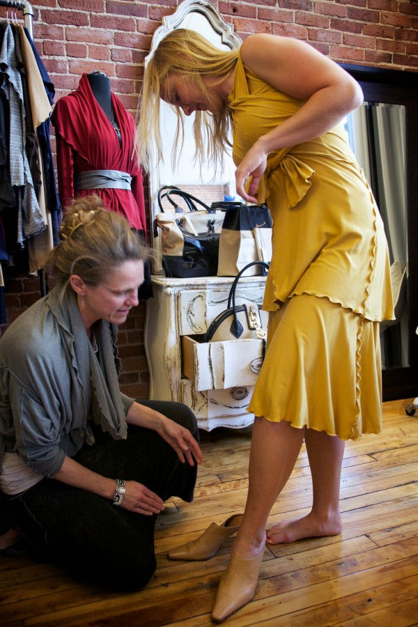 Clothing designer Roxi Suger (left) helps model Paige Mooney pick out some shoes while  trying on a piece from Suger's Angelrox collection in Biddeford on Tuesday. Sugar's creations will grace the catwalk at the Biddeford Ball this weekend.