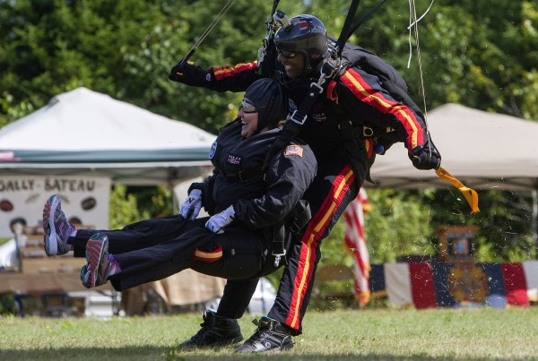 Ann LePage and All Veteran Parachute team member Tony Mouzon come in for a landing after successfully parachuting Aug. 8 as part of the Freedom Fest in Fort Kent.