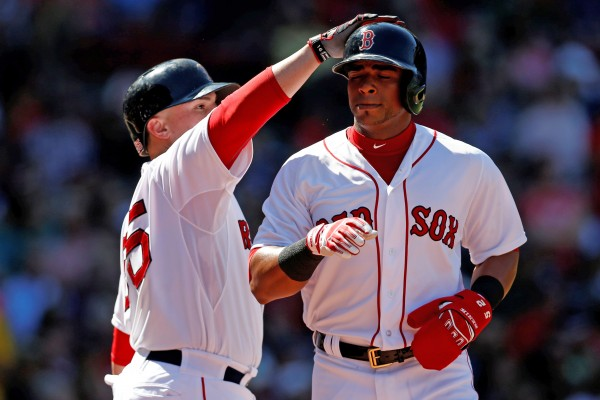 Christian Vazquez of the Boston Red Sox (55) taps Yoenis Cespedes on the helmet during the third inning of Sunday's game against Seattle at Fenway Park. The Mariners won 8-6.