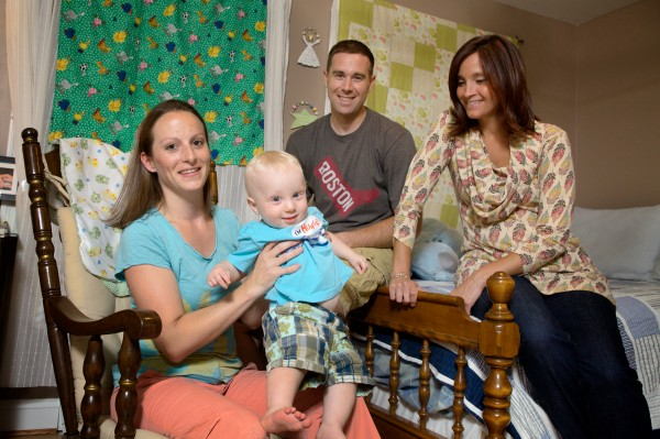 Katie and Chad Bilodeau gather in their son Carter's room in Gray on Friday for a picture with child sleep consultant Jessica Begley (right) who helped them develop a routine to maximize the 11-month-old's sleep time.