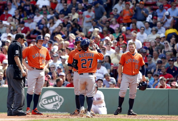 Houston's Jose Altuve (27) touches home plate after hitting a grand-slam against the Boston Red Sox during the second inning at Fenway Park in Boston Sunday .