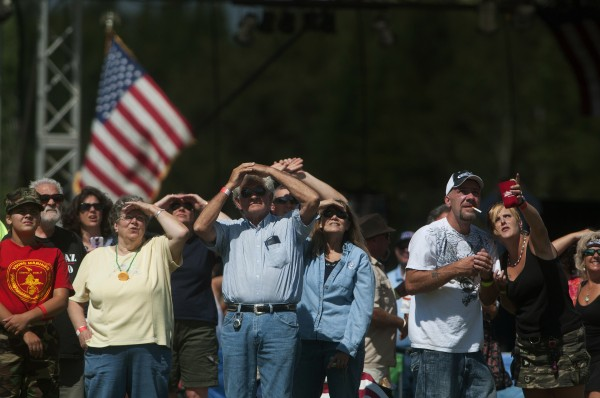Spectators watch as Ann LePage glides back to earth while parachuting with the All Veteran Parachute team Saturday as part of the Freedom Fest in Fort Kent.