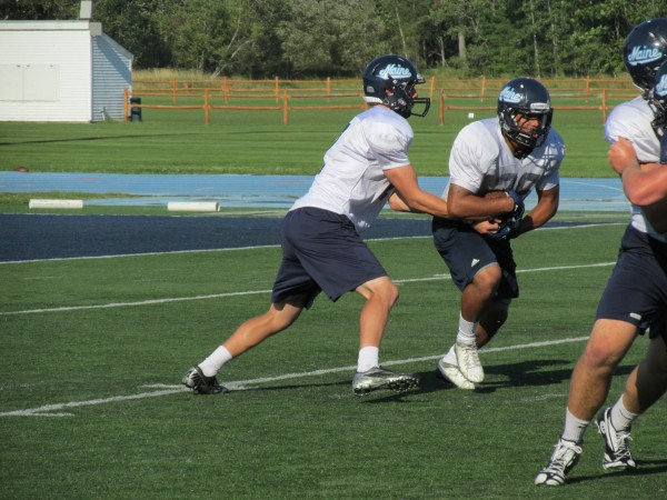 University of Maine quarterback Dan Collins (left) hands off to tailback Nigel Jones during an August practice in Orono.