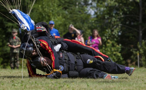 Ann LePage (front) and All Veteran Parachute team member Tony Mouzon laugh after landing after successfully parachuting Saturday as part of the Freedom Fest in Fort Kent.
