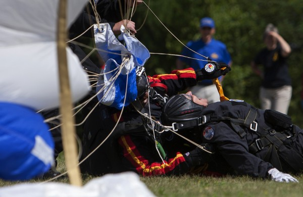 Ann LePage (right) and All Veteran Parachute team member Tony Mouzon laugh after landing after successfully parachuting Saturday as part of the Freedom Fest in Fort Kent.
