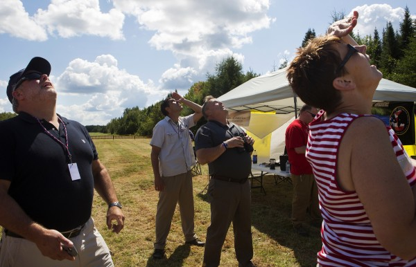 Gov. Paul LePage (center) looks for his wife, Ann LaPage, who jumped out of an airplane with the All Veteran Parachute team Saturday as part of the Freedom Fest in Fort Kent.