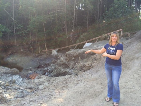Elizabeth Toothaker gestures to the washed-out road that prevents her from driving to her Freeport home. She is on a temporary path used for foot traffic after an Aug. 13 storm destroyed the road.