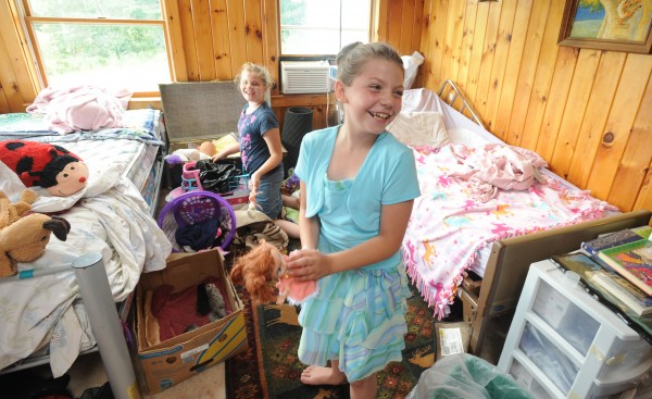 Brianna Spaulding (right) and her sister Julieanna Spaulding play in their room in Belfast on Tuesday.