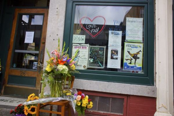 Flowers and signs were placed in front of Paddy Murphy's Irish Pub in downtown Bangor Wednesday after the death of two of the bar's employees, Phill Carter and Roxanne Papken, in a Tuesday evening car crash in Dedham. Several businesses closed for the day in Bangor after the deaths.