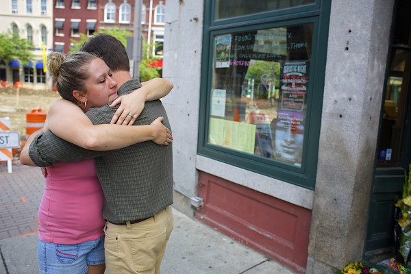 From left, Meghan Black hugs Paddy Murphy's owner John Dobbs while mourning the death of two of pub's employees Wednesday in Bangor. Phill Carter and Roxanne Papken were killed in a crash on Route 1A in Dedham on Tuesday evening.