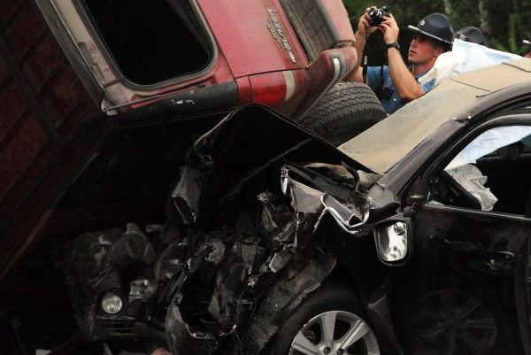 A state trooper takes photos of the crash after a two-vehicle collision on Monday on Route 2 in Winn.