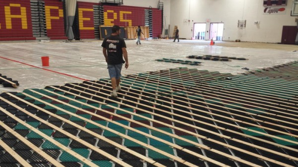 A worker walks across the recycled plastic that will make up the lower layer of Cape Elizabeth High School's new gym flooring. Part of the maple top layer have already been laid.