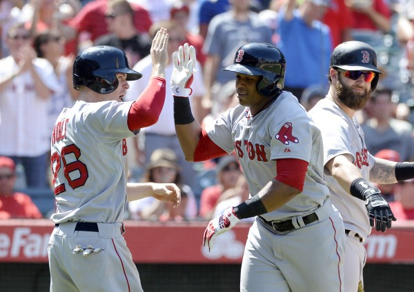 Boston's Yoenis Cespedes (middle) celebrates with Brock Holt after hitting a three-run home run against the Los Angeles Angels in the eighth inning during the game at Angel Stadium of Anaheim.
