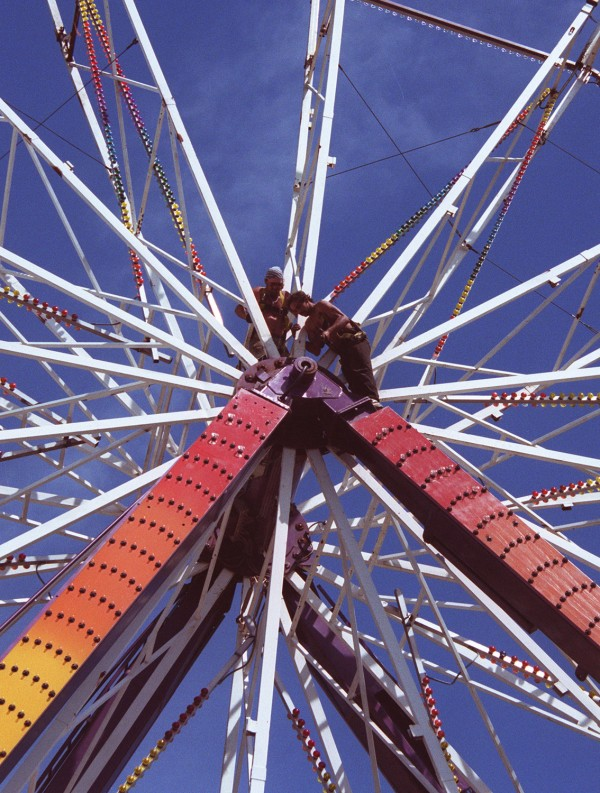 A crew from Smokey's Greater Shows works high above the midway setting up the Ferris wheel at the 2001 Blue Hill Fair Grounds.