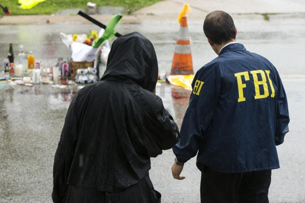 A Federal Bureau of Investigation agent interviews a resident of the neighborhood where teenager Michael Brown was shot in Ferguson, Missouri, on Saturday. In the background is a makeshift memorial for Brown.