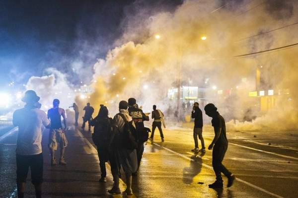 Protesters walk through smoke as police clear a street after the passing of a midnight curfew meant to stem ongoing demonstrations in reaction to the shooting of Michael Brown, in Ferguson, Missouri Aug.17, 2014. U.S. Attorney General Eric Holder ordered a federal autopsy of Brown, a teenager shot dead by a police officer in Ferguson, Missouri, seeking to assure the family and community there will be a thorough investigation into a death that has sparked days of racially charged protests.
