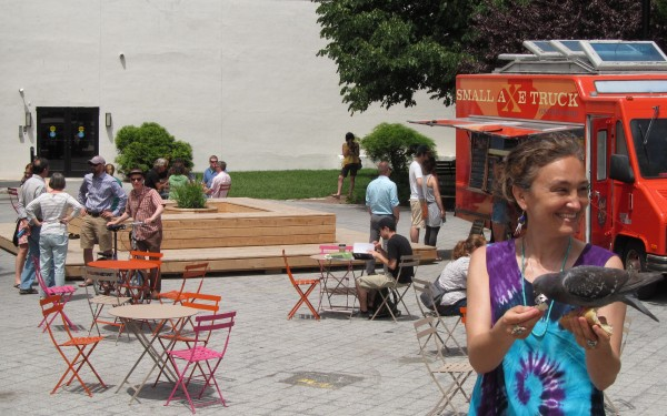 Monique Raymond invites a pigeon to nibble on some bread crumbs in her hand early Wednesday afternoon in Portland's Congress Square while the lunch crowd mingles in the background in this June photo.