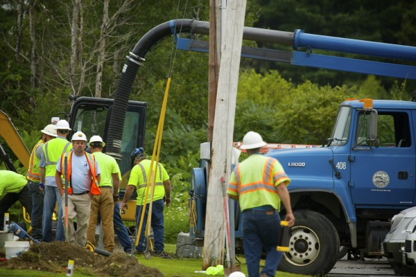 Workers clear dirt near an area where a natural gas leak  closed down parts of Wilson Street Wednesday in Brewer.