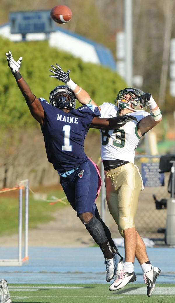 The University of Maine's Axel Ofori Jr. (left) reaches to break up a pass intended for William & Mary's Sean Ballard during their game at Alfond Stadium in Orono on Oct. 19, 2013.
