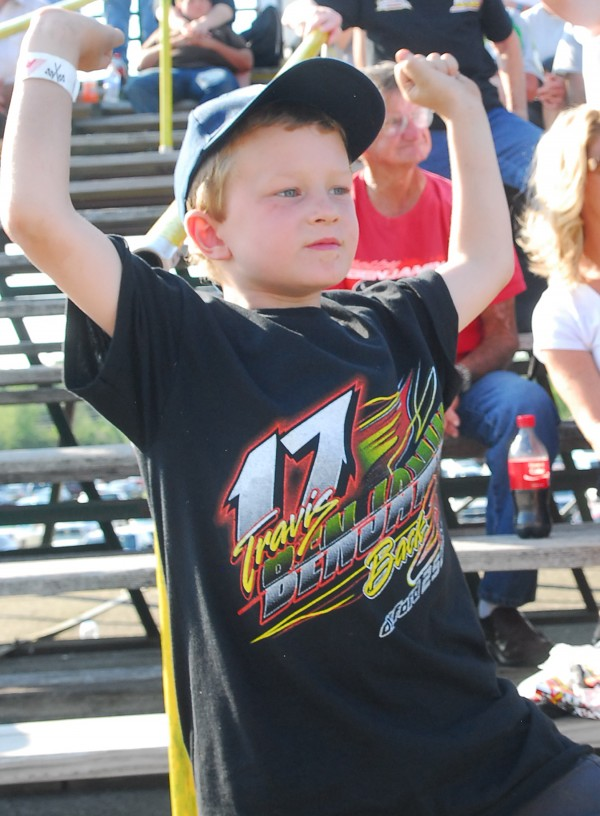 Kaiden Benjamin cheers on his dad, Travis Benjamin, in car 17 Sunday during the Hight 150 race at Speedway 95. Benjamin, from Morrill, went on to finish third. BDN Photo By Terry Farren