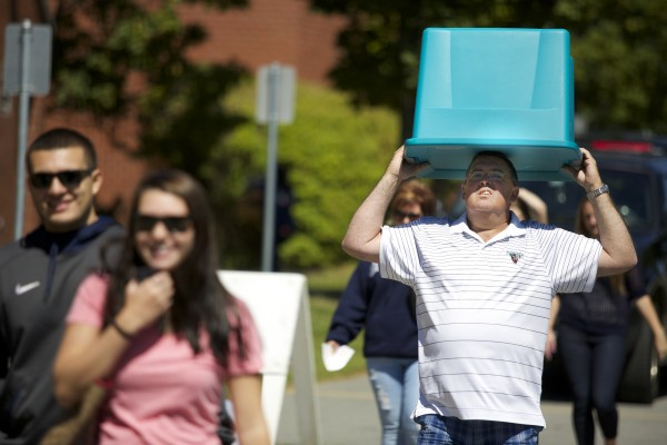 Gary Donovan from Connecticut carries a plastic bin on his head while helping his step daughter move into dorms at the University of Maine.