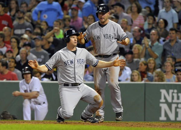 Chase Headley (12) of the New York Yankees reacts with Brian McCann after they scored runs during the fifth inning of Sunday night's game against the Boston Red Sox at Fenway Park in Boston. The Yankees won 8-7.