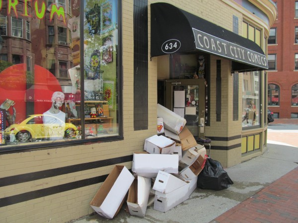Soaked boxes that used to contain comic books are piled up outside the door of Coast City Comics on Congress Street in Portland early Thursday afternoon. Owner Tristan Gallagher said he and others at the store will have to go through 50 long boxes containing about 350 comic books each to see which books are salvageable after his storage area in the basement was flooded with 6-8 inches of water Wednesday night.