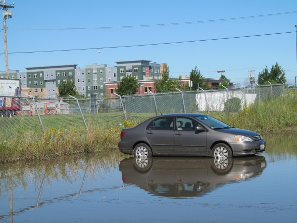 A car is parked in standing water in a lot in Portland's low-lying Bayside neighborhood Thursday morning. The city was hit with more than six inches of rain during a record storm Wednesday.