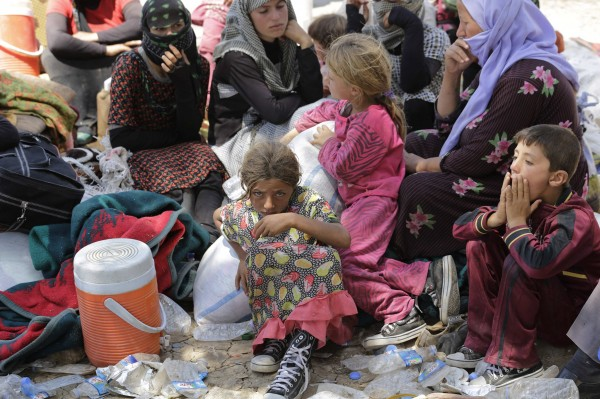 Displaced people from the minority Yazidi sect, fleeing the violence in the Iraqi town of Sinjar, rest on Wednesday at the Iraqi-Syrian border crossing in Fishkhabour, Dohuk province.
