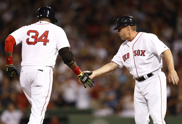 Boston Red Sox third base coach Brian Butterfield (13) celebrates with designated hitter David Ortiz (34) after Ortiz's home run against the Houston Astros during the fifth inning at Fenway Park in Boston Saturday night.