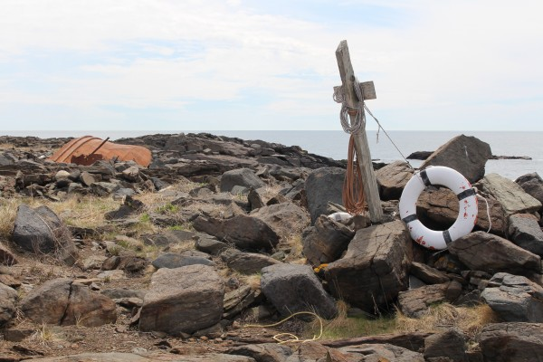 A cross stands by the shipwreck of the D.T. Sheridan at Lobster Cove on Monhegan Island in this May 2014 file photo. Rusty remains of the 110-foot tug boat are scattered along the rocky shore. The ship crashed into the rocks on Nov. 5, 1948. All crew members survived.