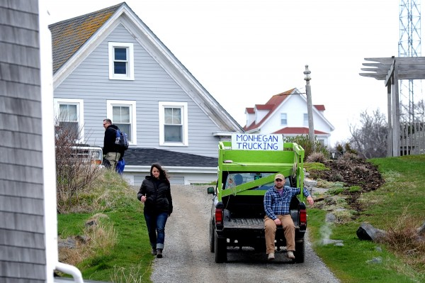 A resident of Monhegan catches a ride on the back of one of the pickup trucks on the island in this May 2014 file photo.