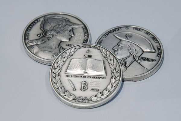 Silver coins etched with the cryptographic information for digital Bitcoins in them lie on a desk during the &quotInside Bitcoins: The Future of Virtual Currency Conference&quot in New York, April 2014.