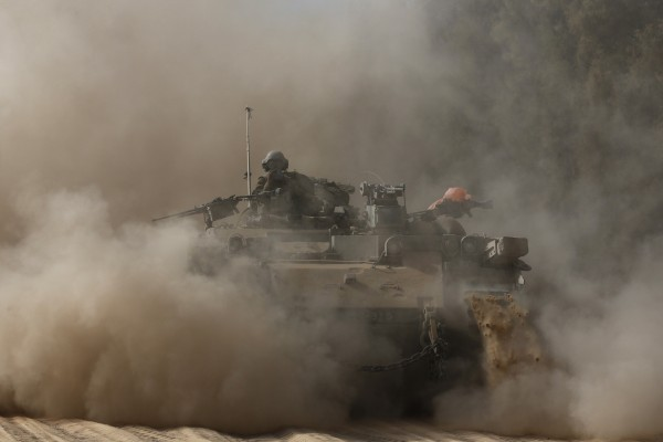 An Israeli soldier rides atop an armored personnel carrier near the border of southern Gaza Strip on Friday.