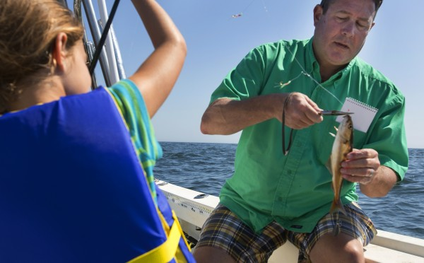 BDN's John Holyoke (right) helps Paige Caron unhook a pollack she caught while on a Tuesday fishing trip in Sedgwick.