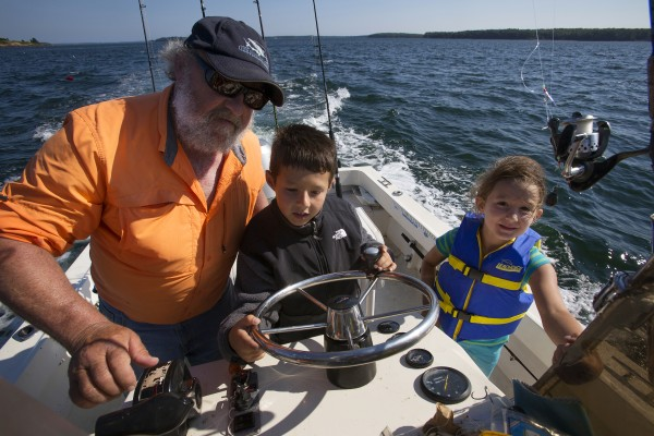 Will Caron (center), 9, gets some help from Capt. Pete Douvarjo (left) while driving his boat as sister, Paige Caron (right), 6, watches during a fishing trip Tuesday in Sedgwick.