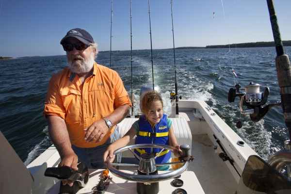 Paige Caron (right), 6, tries her hand at driving Capt. Pete Douvarjo's boat during a fishing trip on Tuesday in Sedgwick.