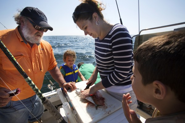 BDN's Sarah Walker Caron (center) learns to clean a mackerel from Capt. Pete Douvarjo (left), while her children, Will Caron (right) and Paige Caron, watch on Tuesday in Sedgwick.