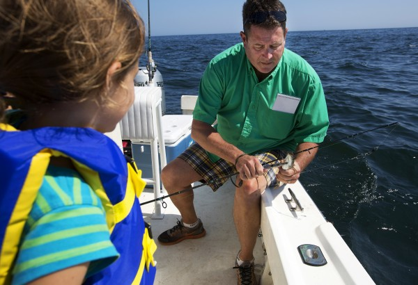 BDN's John Holyoke (right) helps Paige Caron, 6, unhook a pollack she caught while on a Tuesday fishing trip with her mother and brother in Sedgwick.