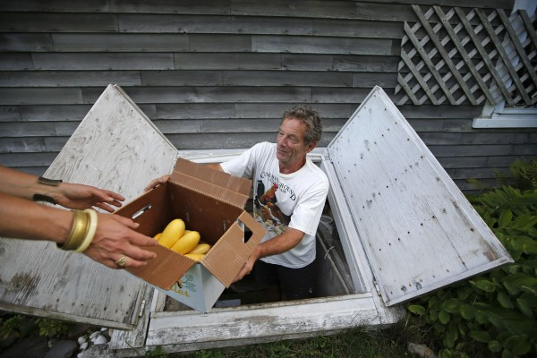 Mike Macfarlane donates a box of summer squash to Hannah Semler at his small farm, Pat and Mike's Garden, in Ellsworth.