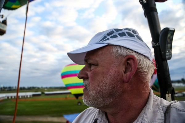 Pilot Ron Cassidy, of New Hampshire, looks over at the rest of the balloons to ensure a clear path to ascend from the ground in Double Exposure during the 11th annual Crown of Maine Balloon Fest in Presque Isle.